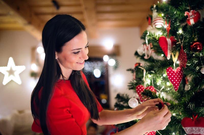 Jovem mulher na frente da árvore de Natal que decora o fotografia de stock