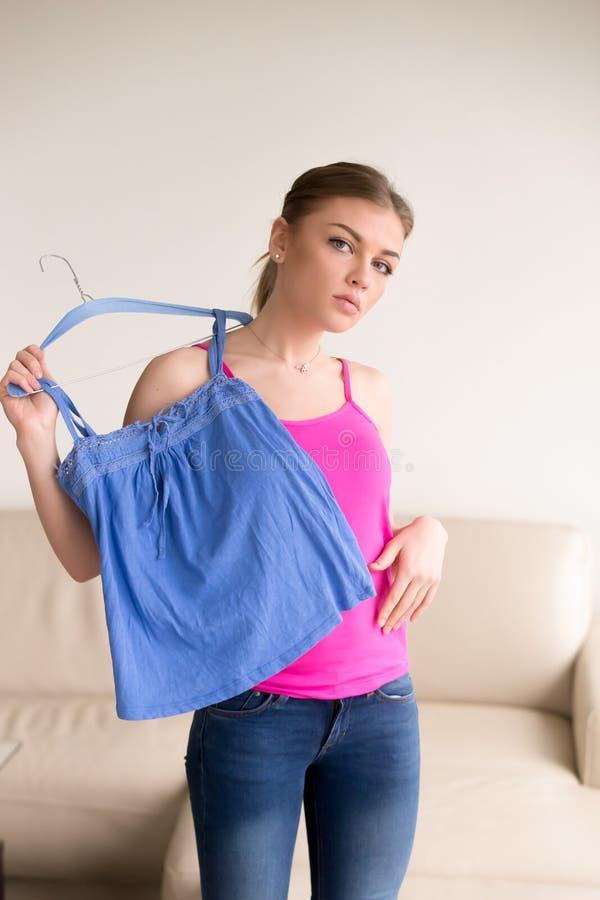 A jovem mulher na frente do espelho tenta sobre a blusa foto de stock
