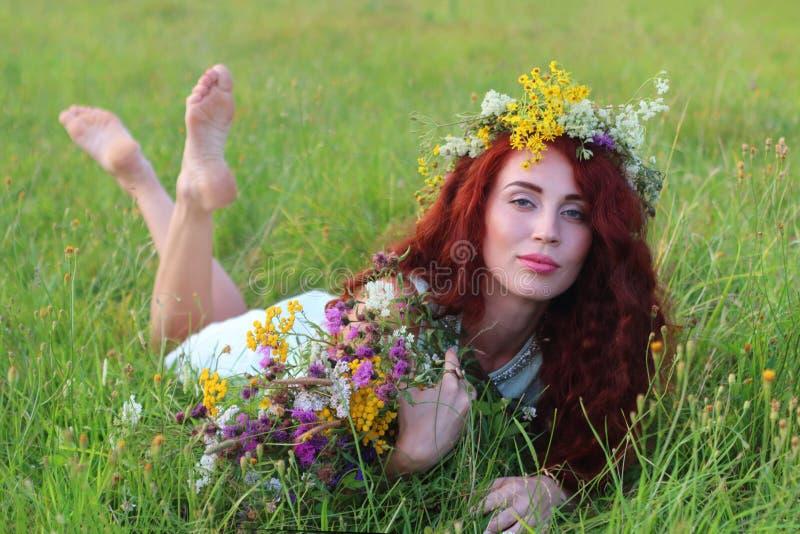 A jovem mulher na grinalda e no vestido encontra-se na grama no prado imagem de stock