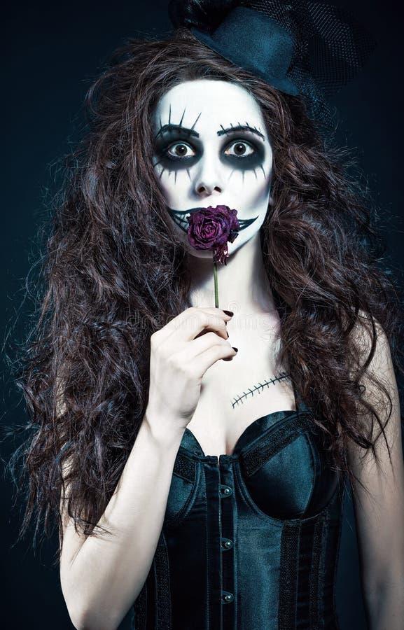 A jovem mulher na imagem do palhaço arrepiante gótico triste guarda a flor murcho foto de stock royalty free