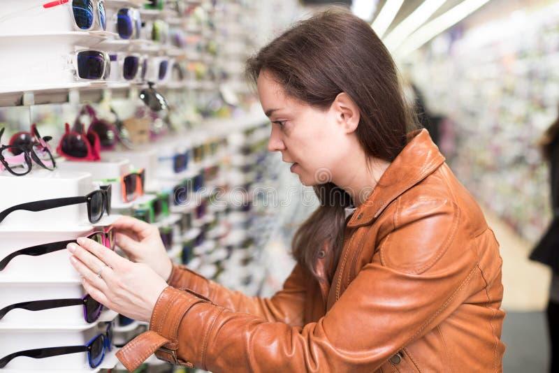 Jovem mulher na loja ótica foto de stock