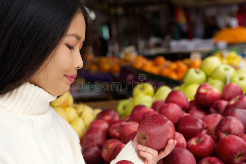 Jovem mulher na loja com maçãs à disposição imagem de stock royalty free