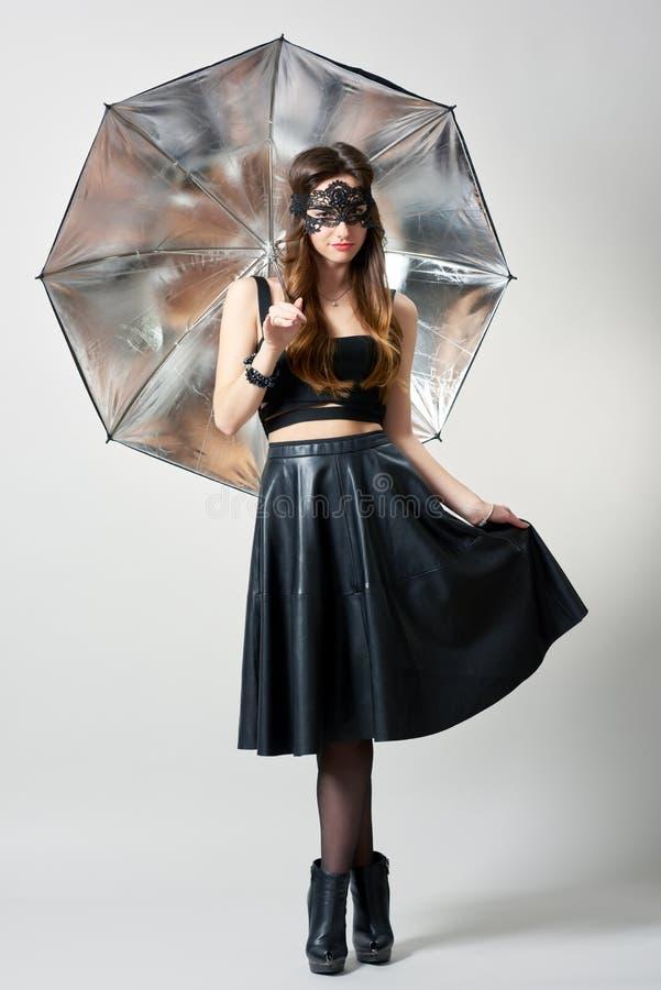 Jovem mulher na máscara do partido com guarda-chuva fotografia de stock