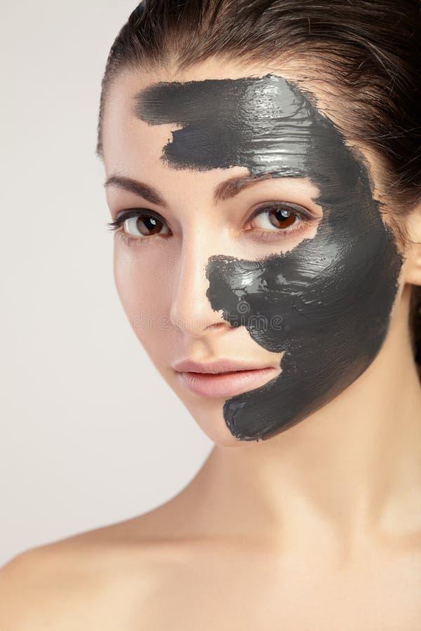 Jovem mulher na máscara para a cara da argila preta imagem de stock