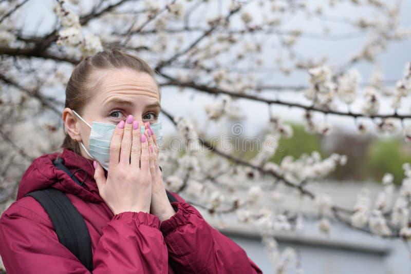 Jovem mulher na máscara protetora médica protetora Árvore de florescência no fundo Alergia da mola imagens de stock royalty free