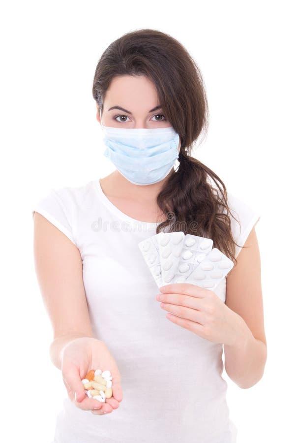 Jovem mulher na máscara que mostra o pacote dos comprimidos isolados no branco fotos de stock royalty free