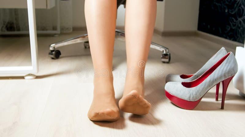 Jovem mulher na meia-calça que move os pés cansados e os dedos do pé após o dia útil no escritório imagens de stock royalty free