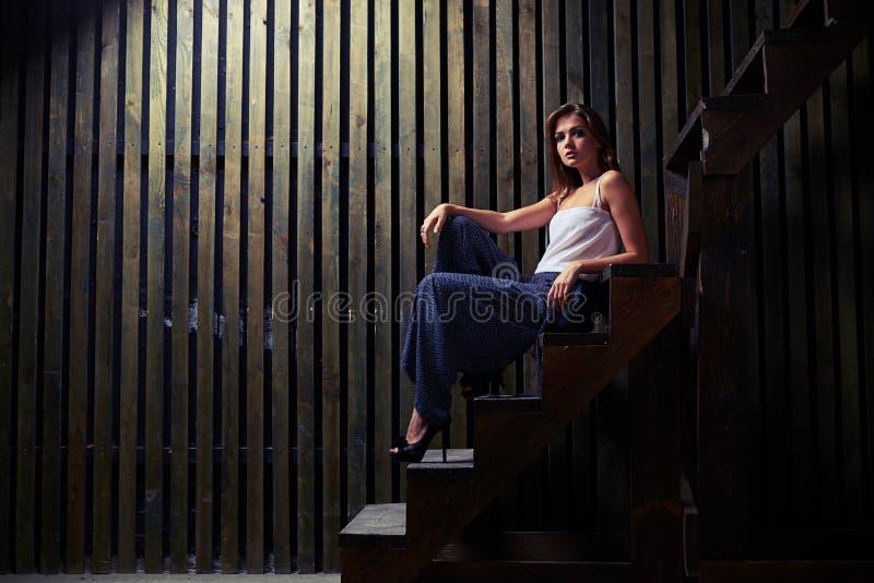 A jovem mulher na moda moderna no salto alto calça o assento em escadas do mim foto de stock