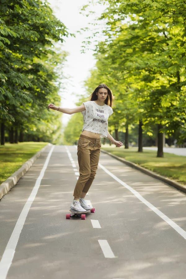 A jovem mulher na moda monta um longboard em um trajeto em um parque fora no verão skateboarding Fora, imagens de stock royalty free