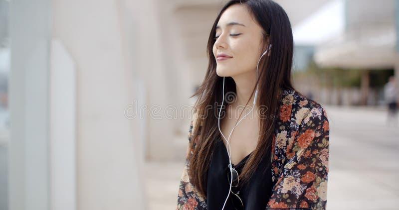 Jovem mulher na moda que escuta a música na cidade fotos de stock