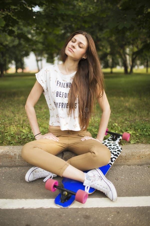 Jovem mulher na moda que senta de pernas cruzadas com o longboard no parque fechado seus olhos e sonhos skateboarding lifestyle fotografia de stock royalty free