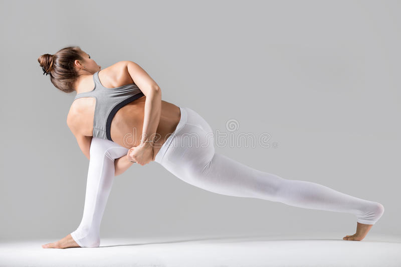 Jovem mulher na opinião traseira da pose de Parivrtta Parsvakonasana, stu cinzento fotografia de stock royalty free
