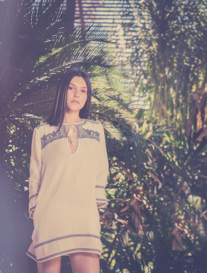 Jovem mulher na palmeira tropical do clima que cerca a foto de stock