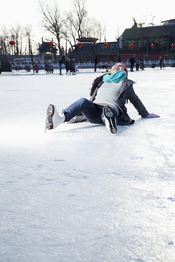 Jovem mulher na pista de gelo, encontrando-se no gelo fotografia de stock royalty free