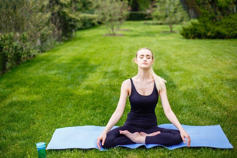 Jovem mulher na pose dos lótus no parque fotografia de stock royalty free