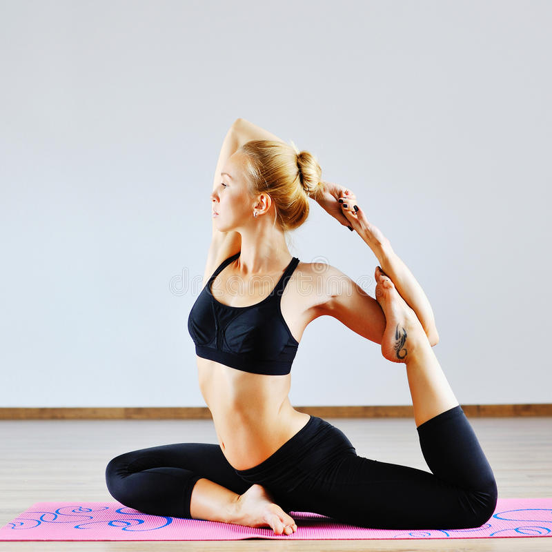 Jovem mulher na posição da ioga dentro foto de stock royalty free