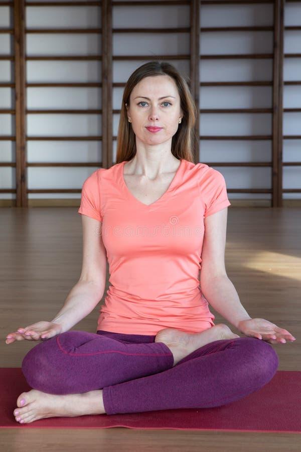 Jovem mulher na posição de lótus ao meditar fotografia de stock royalty free