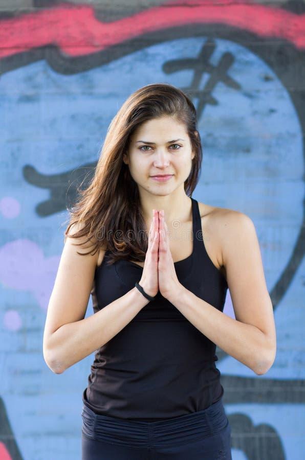 Jovem mulher na posição de Namaste imagem de stock