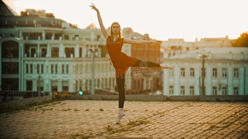 Jovem mulher na posição vermelha da bailarina do vestido na pose graciosa no telhado - construções modernas no fundo - fotografia de stock