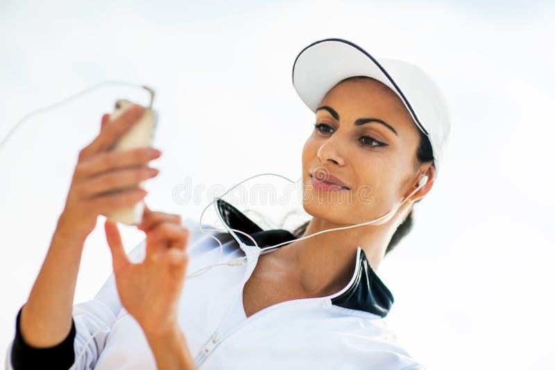 Jovem mulher na praia que escuta a música fotos de stock royalty free