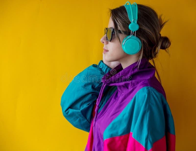 Jovem mulher na roupa do estilo 90s com fones de ouvido imagem de stock