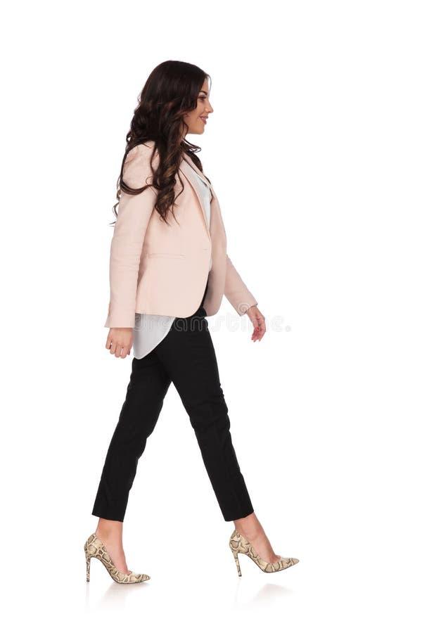 A jovem mulher na roupa do negócio está andando e sorri fotos de stock
