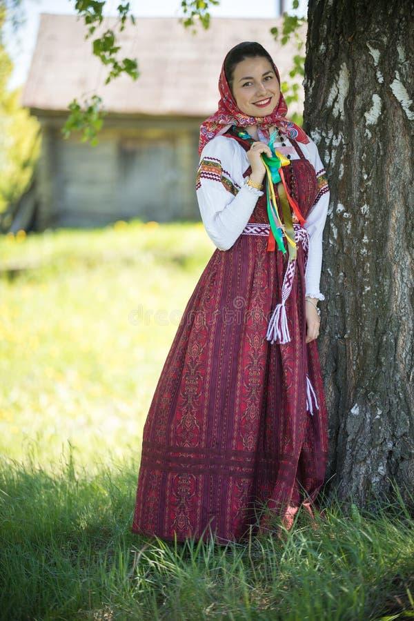 Jovem mulher na roupa tradicional do russo que est? sob uma ?rvore e que guarda sua tran?a imagens de stock royalty free