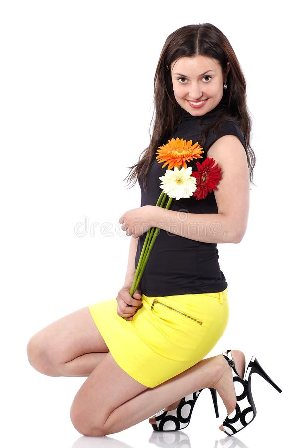 Jovem mulher na saia amarela curto com ocupas dos gerberas no estúdio no fundo branco foto de stock