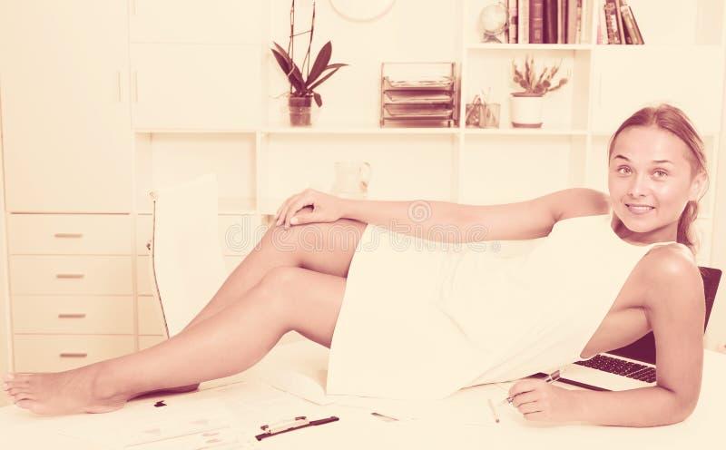 Jovem mulher na tabela no escritório imagem de stock