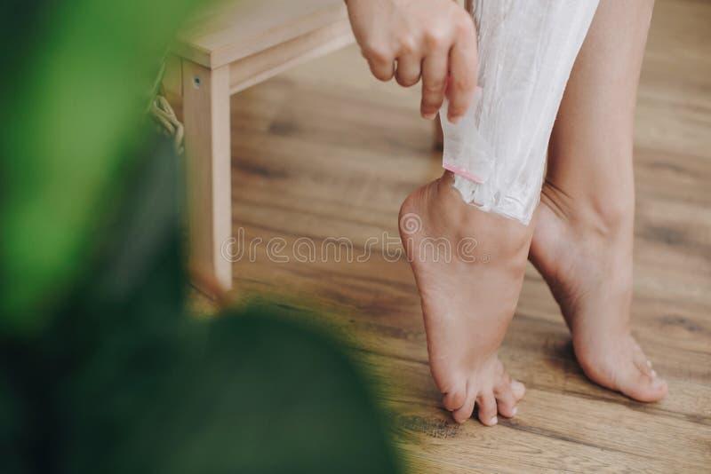 Jovem mulher na toalha branca que aplica o creme de rapagem em seus pés no banheiro da casa com plantas verdes Conceito dos cuida imagem de stock
