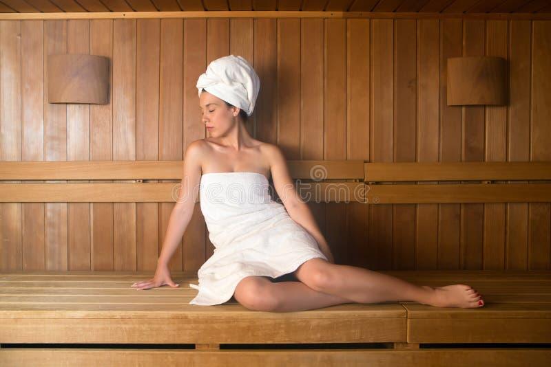 Jovem mulher na toalha que relaxa no banco na sauna fotografia de stock