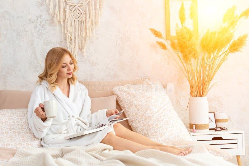 A jovem mulher na veste branca de terry está bebendo o café e está lendo o compartimento ou o livro no quarto fotos de stock