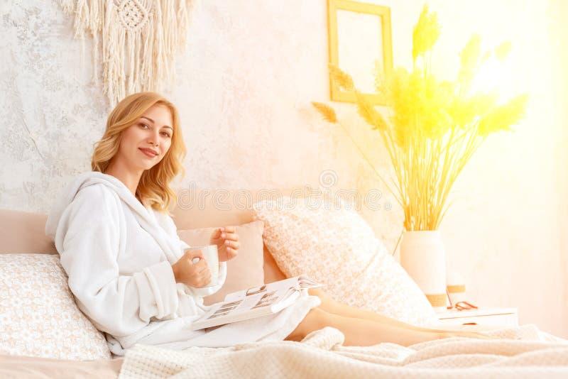 A jovem mulher na veste branca de terry está bebendo o café e está lendo o compartimento ou o livro no quarto fotografia de stock