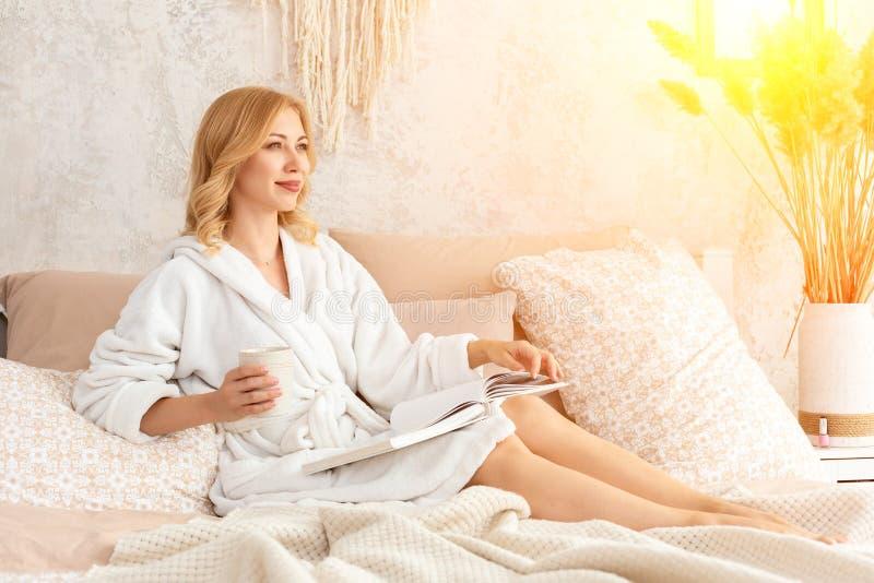 A jovem mulher na veste branca de terry está bebendo o café e está lendo o compartimento ou o livro no quarto fotos de stock royalty free