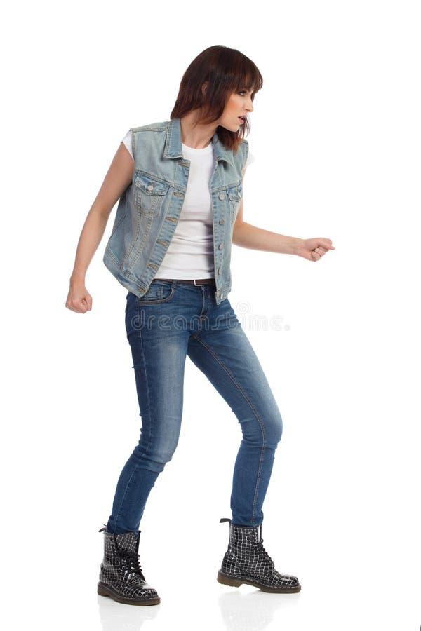 A jovem mulher na veste das calças de brim e em botas pretas Sneaking imagem de stock