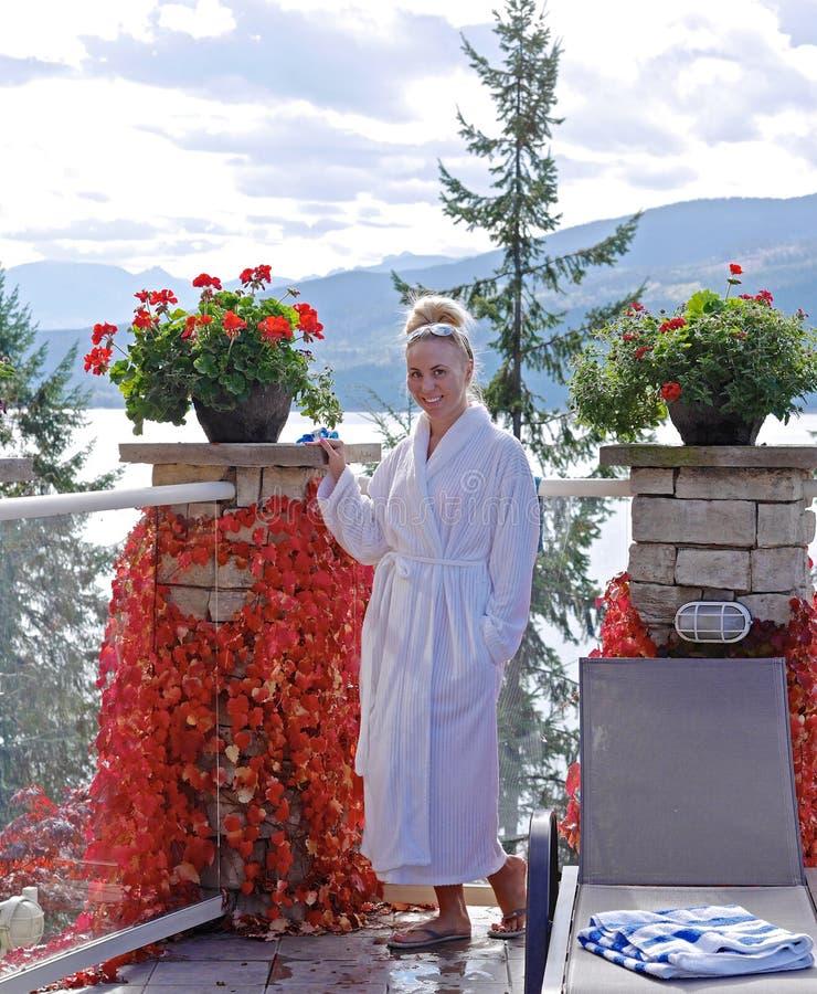 Jovem mulher na veste de banho branca que relaxa pela associação exterior imagem de stock royalty free