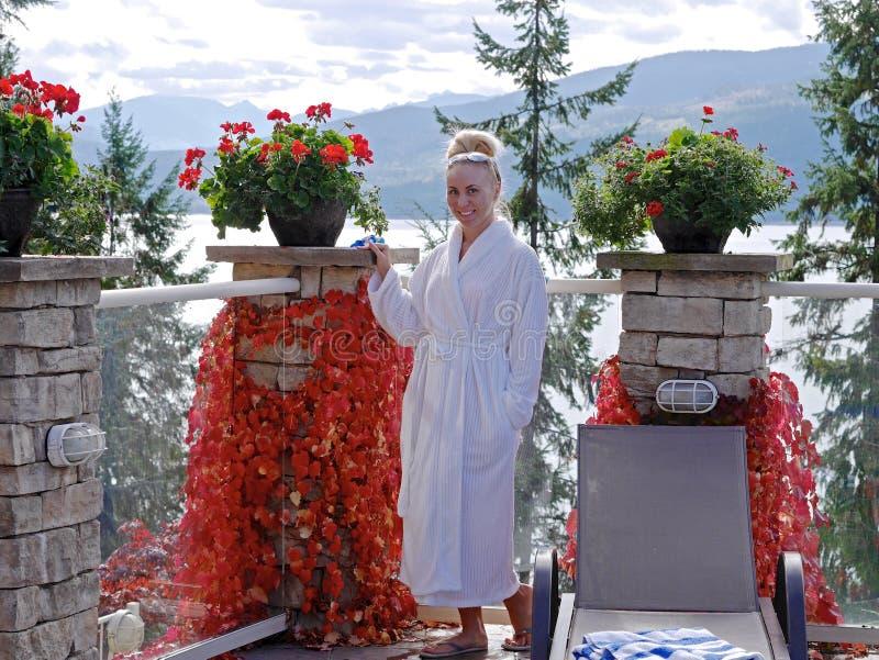 Jovem mulher na veste de banho branca que relaxa pela associação exterior fotografia de stock royalty free