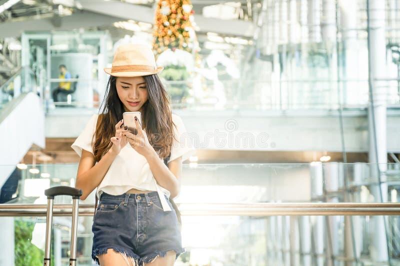 Jovem mulher na viagem aérea de espera do aeroporto usando o telefone esperto fotografia de stock