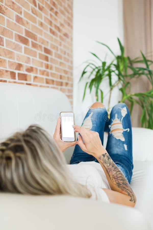 Jovem mulher nas calças de brim que encontram-se no sofá branco e que usam o telefone esperto fotografia de stock royalty free