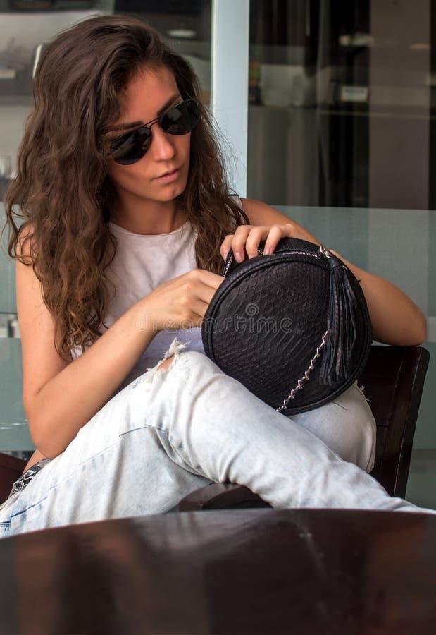 Jovem mulher nas calças de brim vestindo que procuram algo em sua bolsa Jovem mulher que olha dentro de seu saco Terra arrendada  imagem de stock royalty free