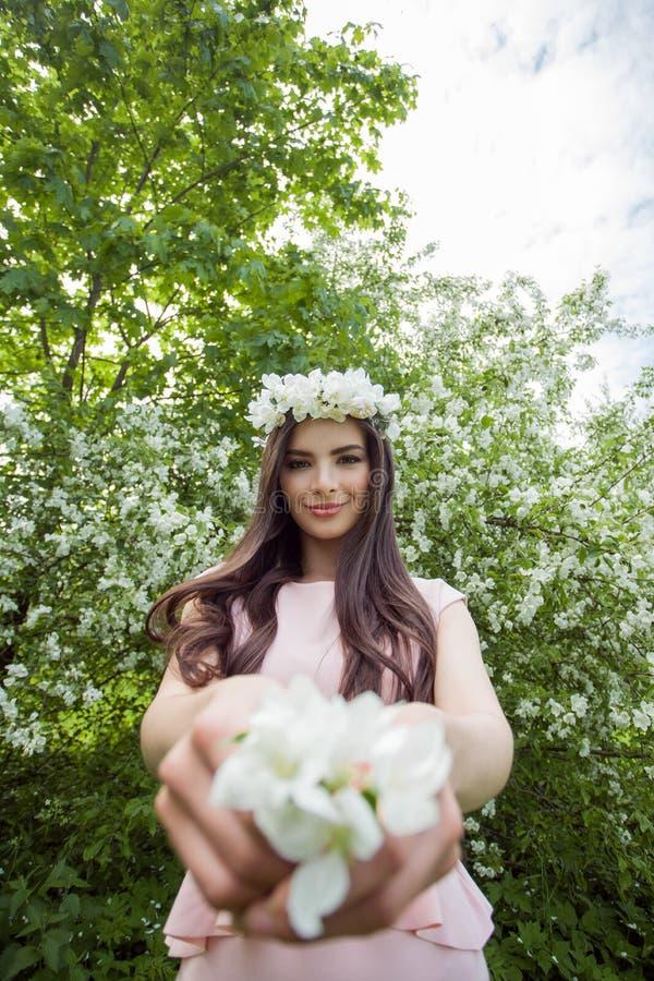 A jovem mulher nas flores envolve-se no parque da flor da mola fora Retrato exterior da menina bonita no fundo da folha fotos de stock
