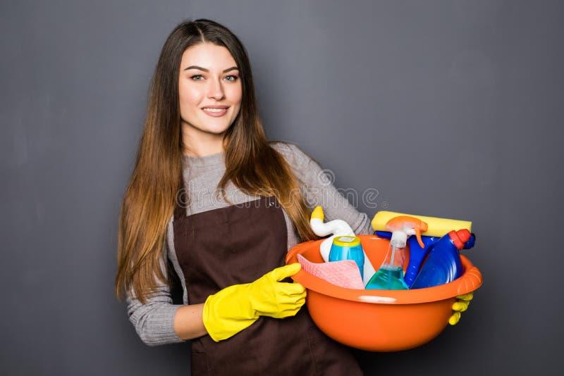 Jovem mulher nas luvas protetoras que guardam uma cubeta com coisas para limpar e que sorriem no fundo cinzento imagem de stock royalty free