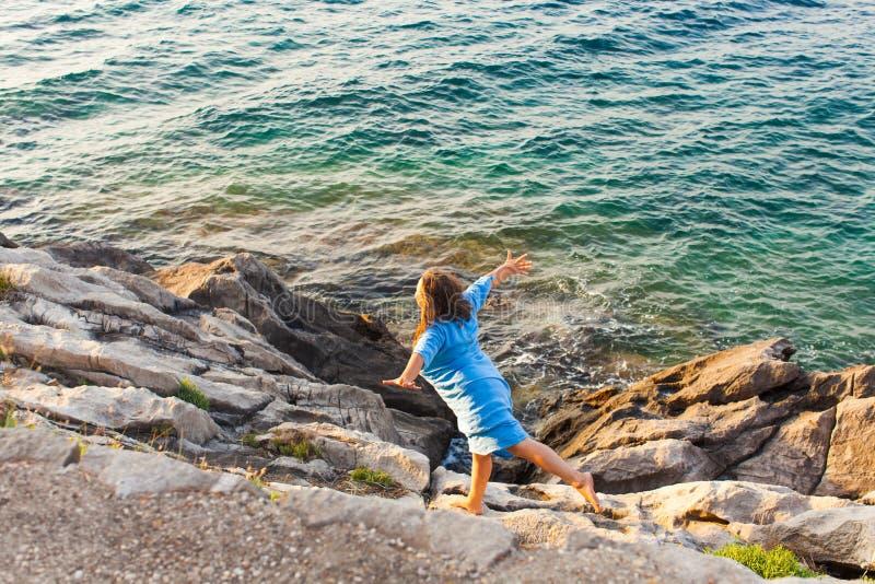 Jovem mulher nas rochas acima do mar imagens de stock royalty free