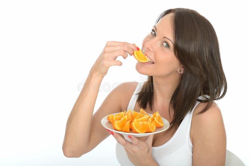 Jovem mulher natural feliz saudável que come uma placa de segmentos alaranjados maduros frescos imagens de stock royalty free