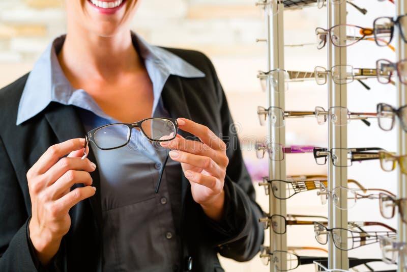 Jovem mulher no óptico com vidros fotos de stock