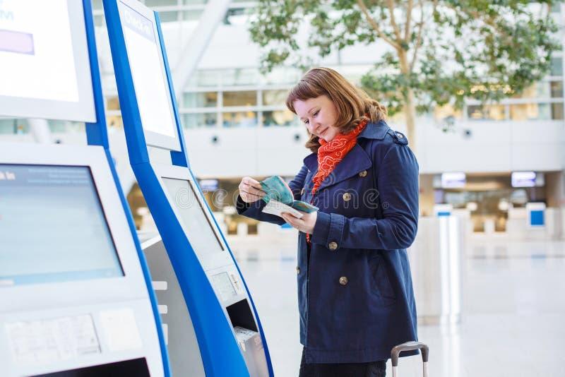 A jovem mulher no aeroporto internacional que faz eletrônico verifica dentro imagem de stock royalty free
