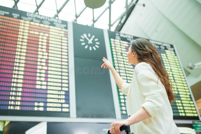 Jovem mulher no aeroporto internacional que olha a placa da informação do voo que verifica para ver se há o voo imagem de stock royalty free