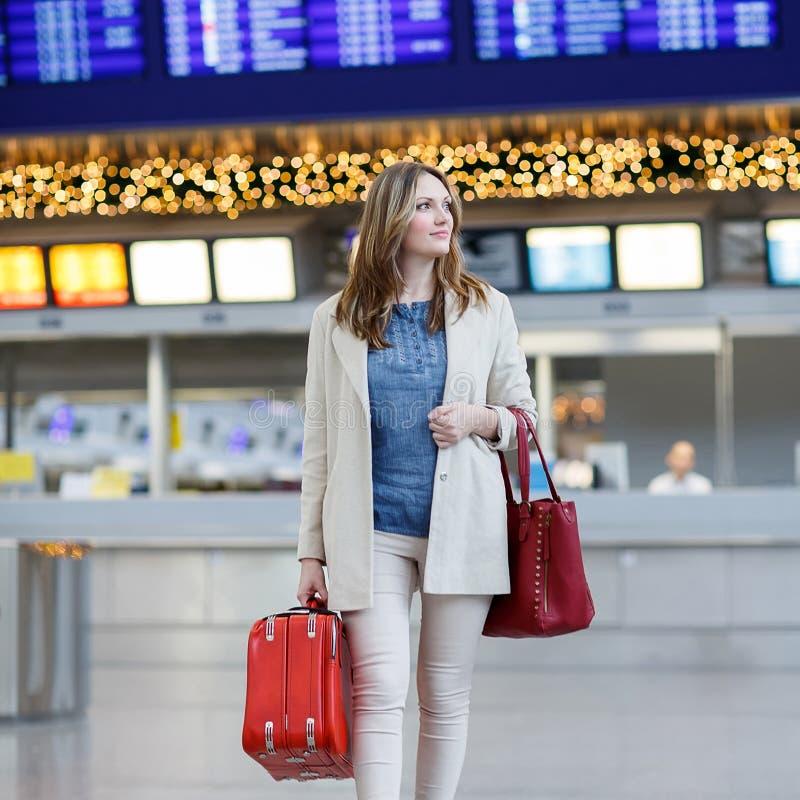 A jovem mulher no aeroporto internacional, vai à porta imagens de stock