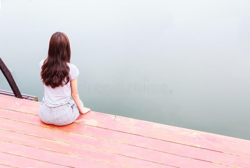 Jovem mulher no assento das férias de verão descansadamente no cais de madeira com fundo da água no reservatório da represa Ambie imagem de stock