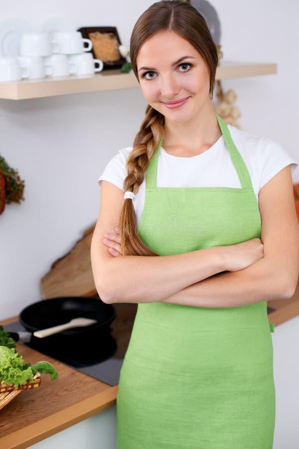 A jovem mulher no avental verde está indo cozinhando em uma cozinha A dona de casa está provando a sopa pela colher de madeira fotos de stock royalty free